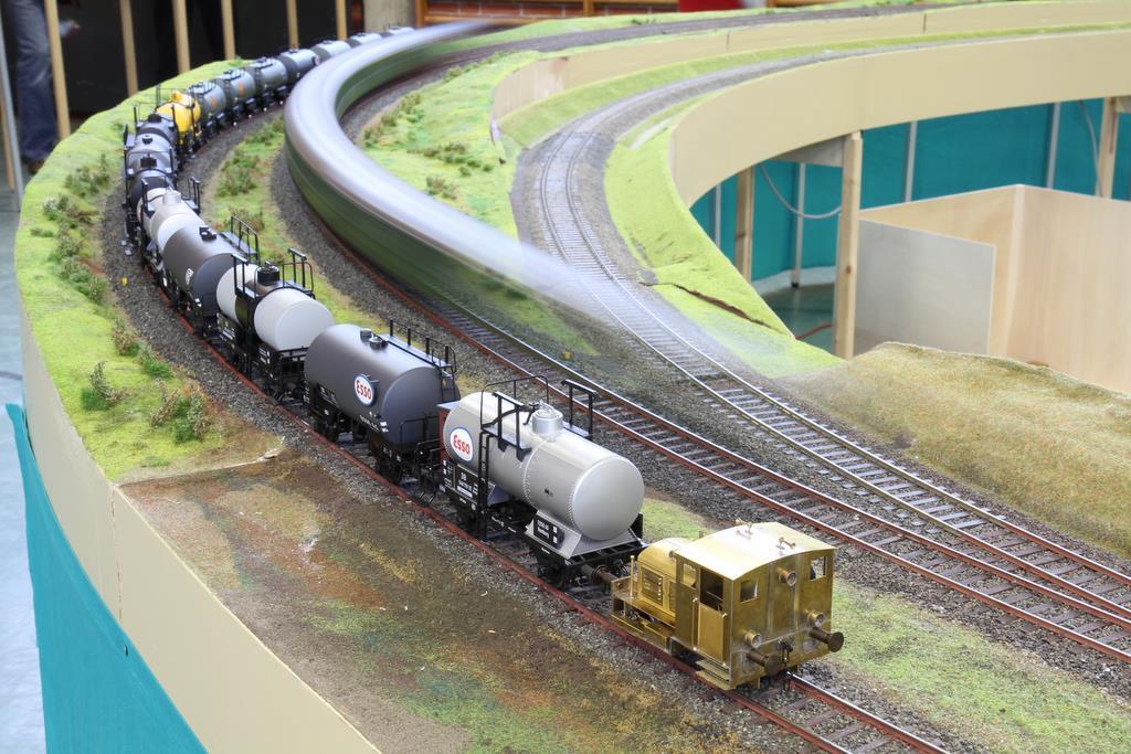 Die kleine Deutz Rangierlok müht sich mit dem Kesselwagenzug, auf dem Gegengleis huscht ein Zug vorbei.