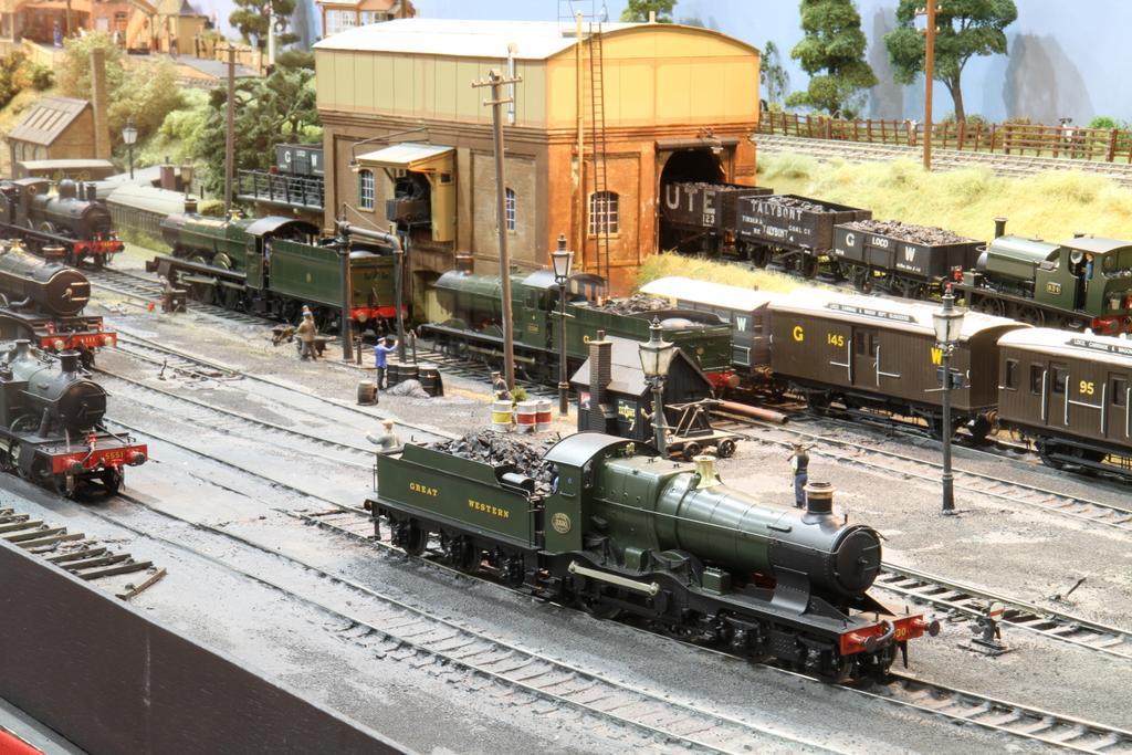 Dampfloks rangieren im Vordergrund, rollende Züge im Hintergrund