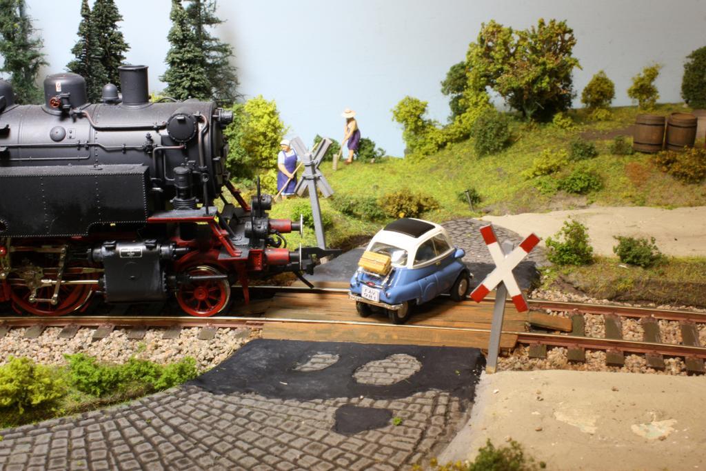 Filmszene: Das Filmteam in der Isetta flitzt vor dem Filmzug über den Bahnübergang