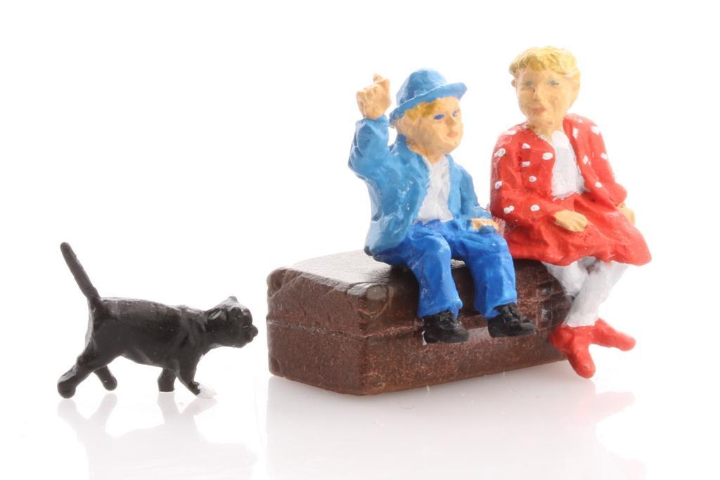 Hauser Figuren: Kinder auf einem Koffer sitzend